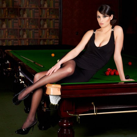 Glamorous brunette sexy woman sitting on a snooker table photo