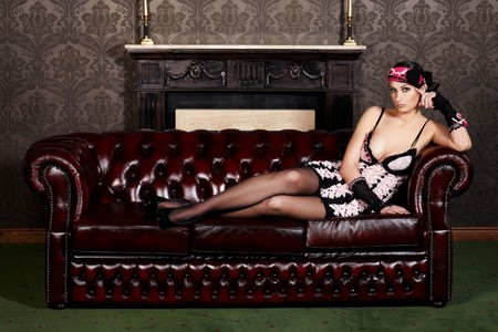 Sexy brunette lady on a sofa in old fashioned interior photo