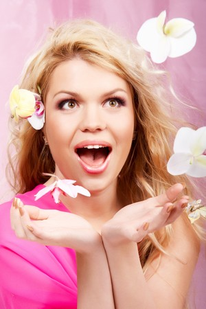 Young lady catching falling orchids photo