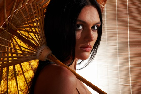 jalousie: Sexy tanned brunette woman with wet umbrella in the sunlight going through wooden jalousie