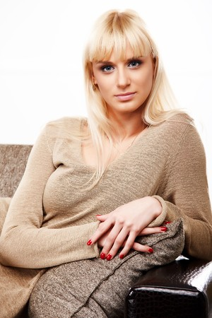 Portrait of beautiful happy lady with blue eyes in beige sweater sitting on a sofa photo