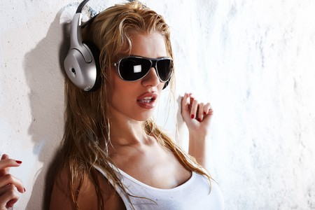 Wet babe in white shirt and sunglasses listening for the music using headphones Stock Photo - 7178297