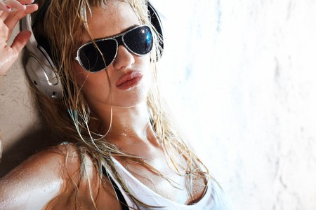 Wet babe in white shirt and sunglasses listening for the music using headphones photo