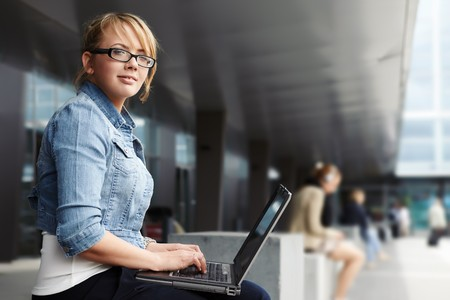 Young lady sitting in a modern cityscape with laptop photo