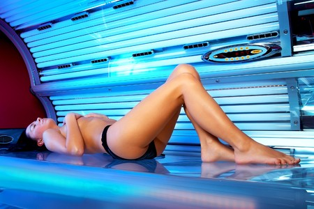 Beautiful young woman tanning in solarium  photo