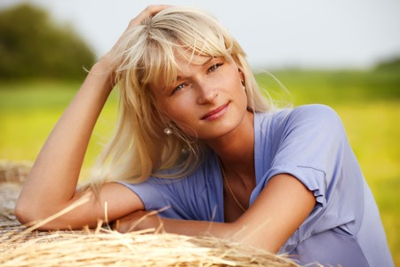 Young blond girl lean on a haystack photo