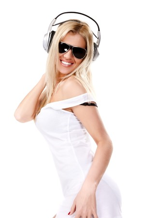 Sexy woman in white shirt and sunglasses listening for the music using headphones photo