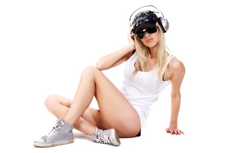 sexy headphones: Sexy woman in white shirt and sunglasses sitting on a floor and listening for a music using headphones Stock Photo