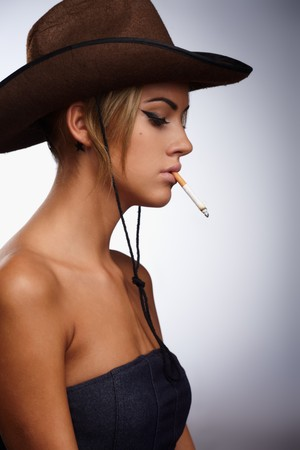 Young lady in a cowboy hat holding a cigarette in her mouth photo