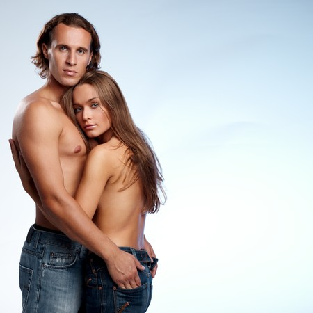 woman nude standing: Young couple in blue jeans on blue background