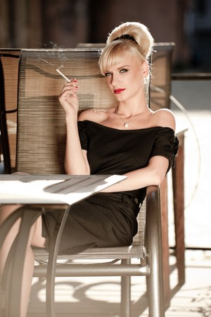 glamorous: 50s styled woman sitting in a street cafe and smoking cigarette