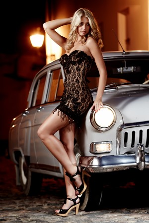Beautiful lady in black dress standing next to oldtimer car in the night city Stock Photo - 8251529