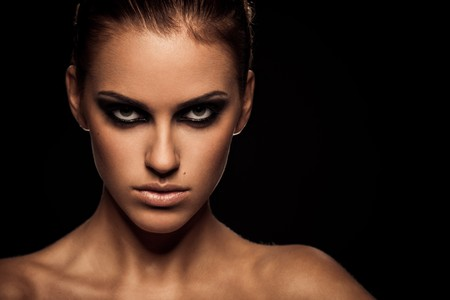 Closeup portrait of a serious lady with smoky eye makeup photo