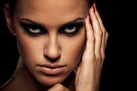 Closeup portrait of a serious lady with smoky eye makeup Stock Photo - 8338987