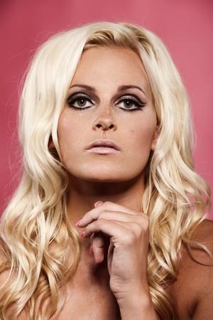 Closeup portrait of a blond lady on pink background photo