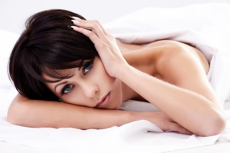 Closeup portrait of a young brunette woman lying in bed photo