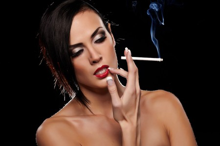 Elegant brunette woman smoking a cigarette on black background Stock Photo - 8326865