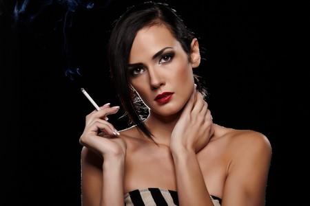 Elegant brunette woman smoking a cigarette on black background photo