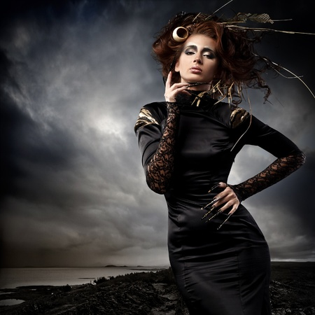 High fashion model in black dress, with long nails and creative hairstyling and makeup in stormy weather photo
