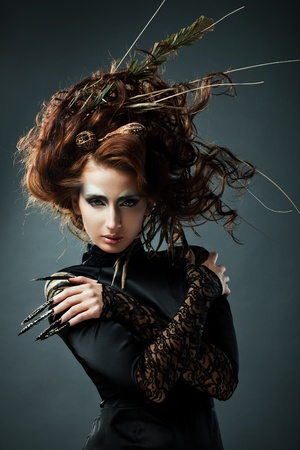 High fashion model in black dress, with long nails and creative hairstyling on grey background photo