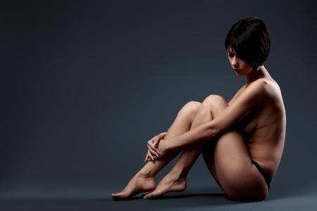 femme noire nue: Jeune femme belle assis sur un plancher de