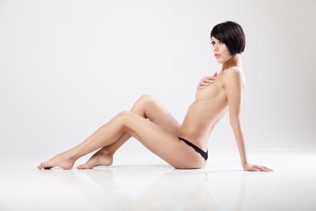 mujeres eroticas: Joven y hermosa mujer sentada en un suelo