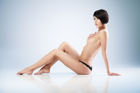 erotic girl: Young beautiful woman on blue background Stock Photo