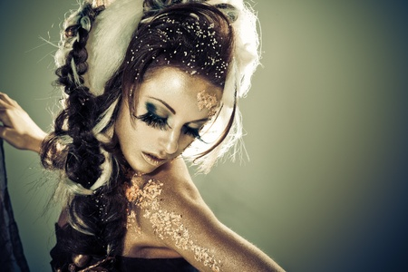 Vogue style portrait of a woman with gold-silver bodyart and makeup photo
