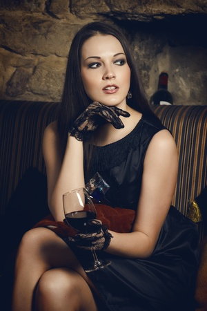 Woman sitting on a couch and holding a glass of wine Stock Photo - 8900548