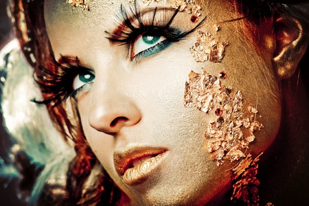 Vogue style portrait of a woman with gold makeup photo