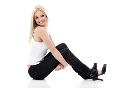 sitting on floor: Smiling sexy blond woman in white shirt and  jeans sitting on a floor isolated on white