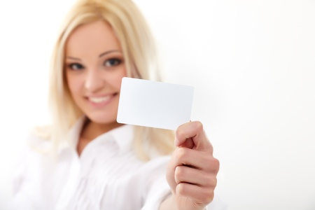 Happy blond woman showing blank credit card. Focus on card. photo
