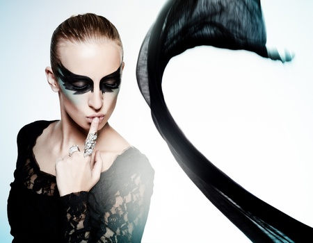 Vogue style portrait of a young woman with fantasy makeup and a fluttering fabric on background photo