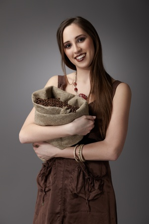 Woman with a burlap sack of coffee beans on gray background photo
