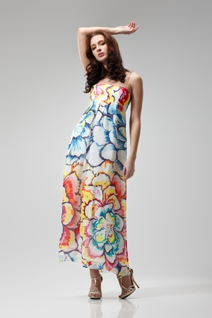 Young beautiful female model in colorful dress on gray background photo
