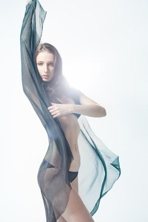 tela seda: Hermosa joven est� ocultando su rostro detr�s de una pieza de tela de seda Foto de archivo
