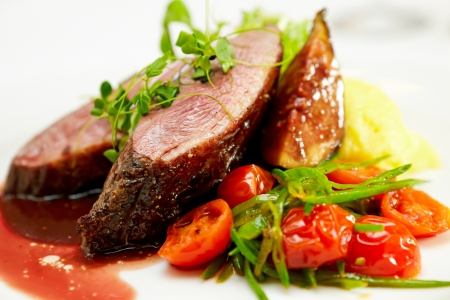 Glazed duck fillet, mashed potatoes seasoned with truffle oil, fig and aniseed sauce Foto de archivo