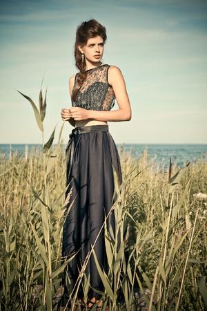 Young woman wearing purple dress in a meadow near the sea photo