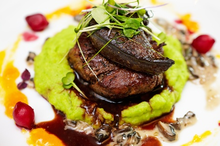 Fillet of beef with elk liver served with mashed potatoes and peas, creamy mushroom stew and red wine and blueberry sauce photo