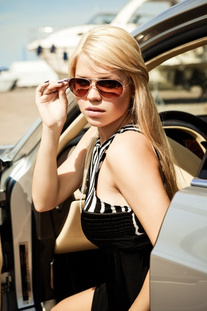 Car and babeYoung sexy blond girl sitting in a luxury car photo