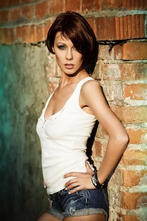 короткие волосы: Сексуальная брюнетка Дама в белой рубашке стоит возле кирпичной стены