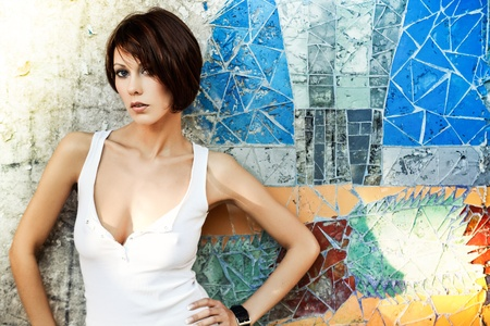 woman short hair: Sexy brunette lady in white shirt standing near a brick wall Stock Photo