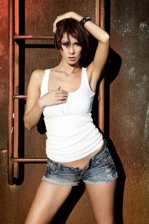 hot babe: Sexy brunette lady in white shirt standing near a brick wall Stock Photo