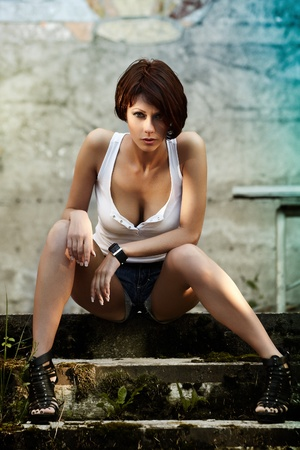 babe: Sexy brunette lady in white shirt sitting on stairs