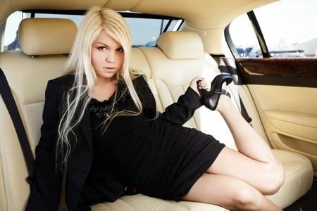 Jeune femme blonde assise sur une banquette arrière d'une voiture de luxe Banque d'images - 10253414