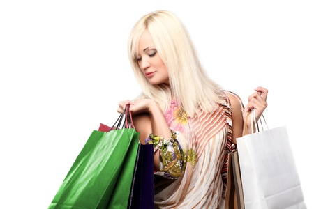 Young blond lady holding shopping bags isolated on white photo