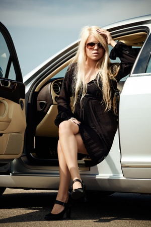 Car and young sexy blond girl sitting in a luxury car photo