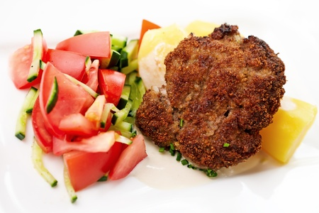 minced: Minced meat cutlet with boiled potatoes and tomato-cucumber salad Stock Photo