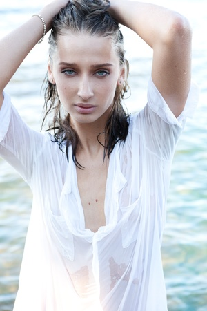Young lady with wet hair in white shirt coming out of the sea photo