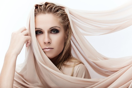 Portrait of a young beautiful lady covered with beige fabrics photo